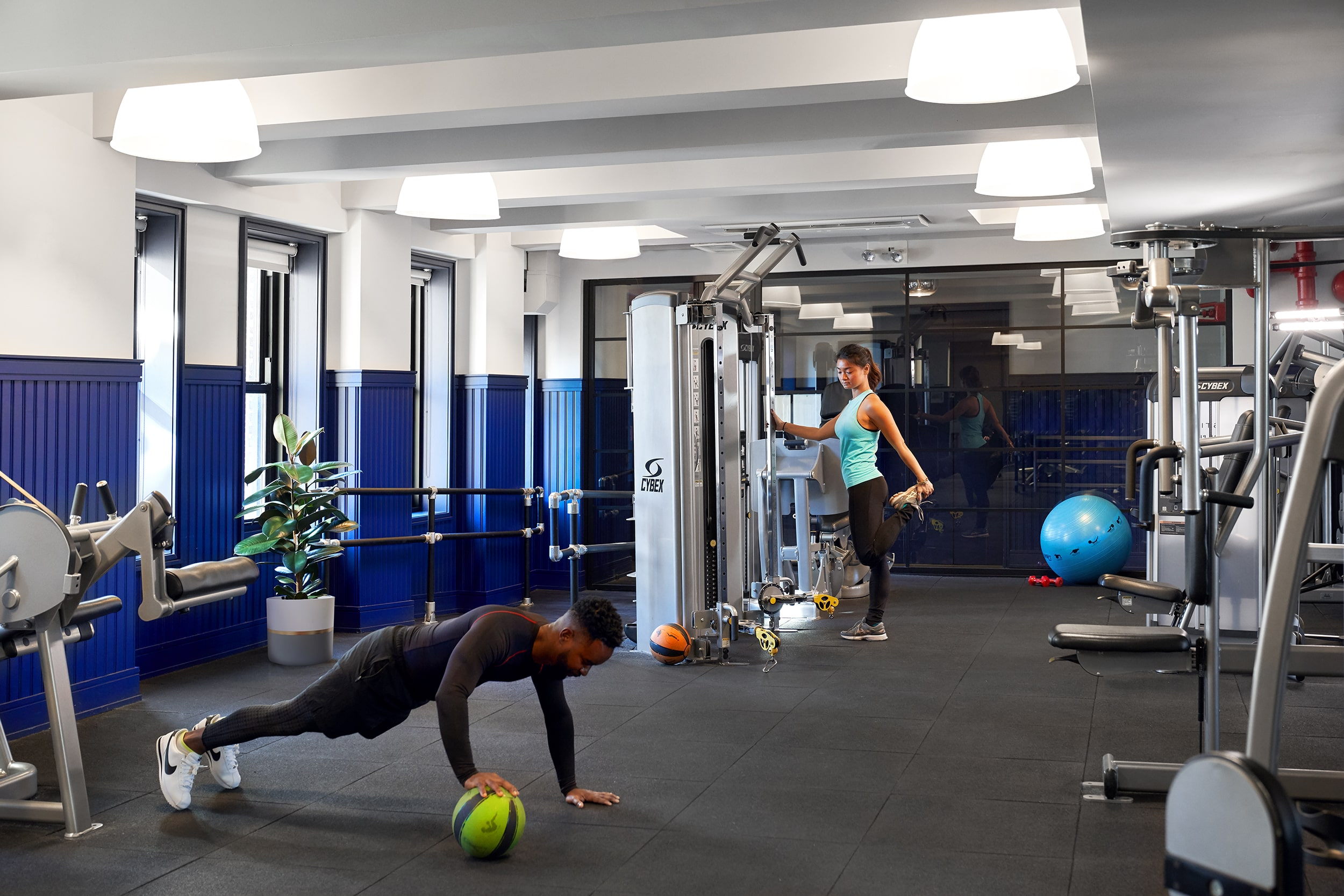 Man and woman working out and stretching in the gym